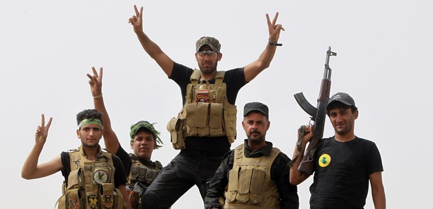 """Iraqi Shiite fighters from the Popular Mobilisation units flash the """"V"""" for victory sign in the town of Baiji, north of Tikrit, as they fight alongside Iraqi forces against the Islamic State (IS) jihadist group to try to retake the strategic northern Iraqi town for a second time, on June 10, 2015. Baghdad regained control of Baiji -- located on the road to IS hub Mosul and near the country's largest oil refinery -- last year, but subsequently lost it again. AFP PHOTO / AHMAD AL-RUBAYE        (Photo credit should read AHMAD AL-RUBAYE/AFP/Getty Images)"""
